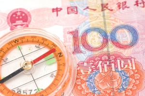 A compass sitting on a 100 Renminbi note